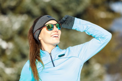 Girl wearing sportswear looking at the sky and smiling. Winter sports, outdoor fitness, fashion, workout, health concept.