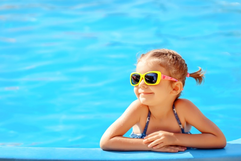 Smiling cute little girl in sunglasses in pool in sunny day.