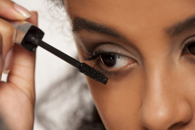 portrait of a young dark-skinned woman applying makeup on a white background
