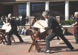 Photograph of VCU Taiko, a Japanese barrel drumming group, performing at the VCU Cherry Blossom Festival at the student commons.