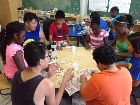 Campers in the beginning stages of building birdhouses.