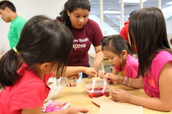 Kids are making jell-o with the help of their Focus on Youth counselor.