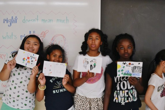Campers showing off their drawings about themselves.