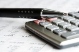Closeup of a pen resting on a calculator