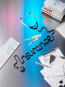 """Abstract insurance-related graphic, showing a stethoscope on a desk with its cord twisted into the cursive word """"insurance"""""""