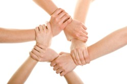 A circle of six hands holding each other by the wrist
