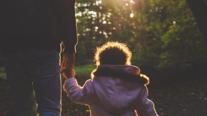 pappa håller barn i handen på promenad