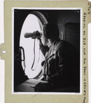 Photograph of a man with binoculars sitting in an airplan conducting an aerial search for icebergs.