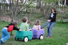 Children pulling one another in a toy with wheels.