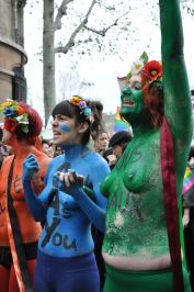 Three women, painted orange, blue and green, one with her fist up in the air, members of Femen protesting for marriage equality.