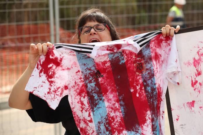 Militante da causa palestina protesta e mostra camisa da seleção pintada de vermelho em frente ao CT do Barcelona, durante treino da seleção argentina