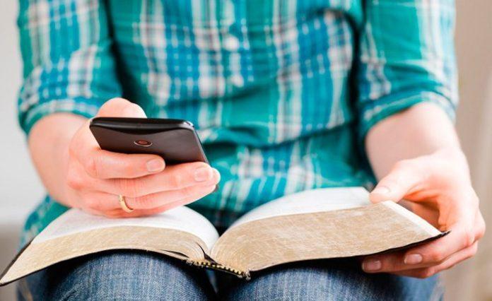 Jovem com uma Bíblia e um celular