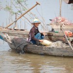 Fisherman sitting in riverboat, Cambodia