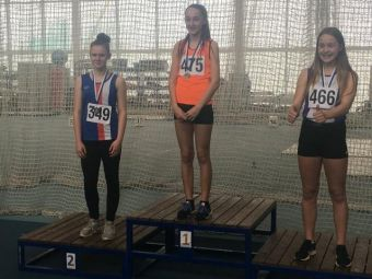 Catrina MacArthur stands at the podium after winning silver for the 60m hurdles.