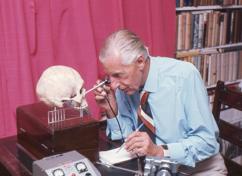 Calvin Wells examining a human skull in his office at White Horse Cottage Norwich, c1975 [Calvin Wells Archive, Ref code: CAL/