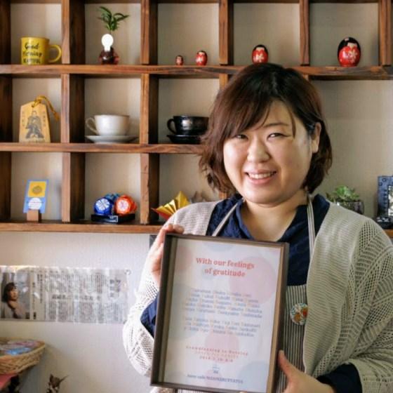 クラウドファンディングの支援者を名前を手にする箱カフェまんまる茶茶の橋田祐理子さん