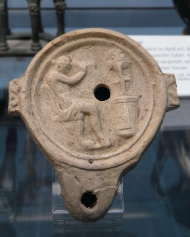 Terracotta oil lamp depicting Apollo seated with tripod, 2nd century AD