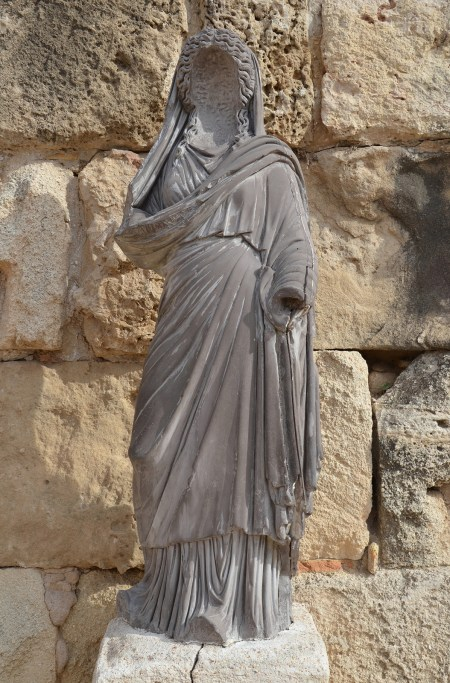 Statue of a female figure in grey marble, its face, hands and feet were white marble insets and are now missing, this type is usually identified with Persephone, Salamis