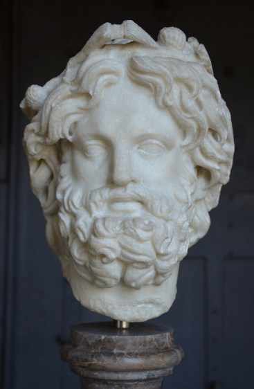 Head of Silvanus crowned with pine.