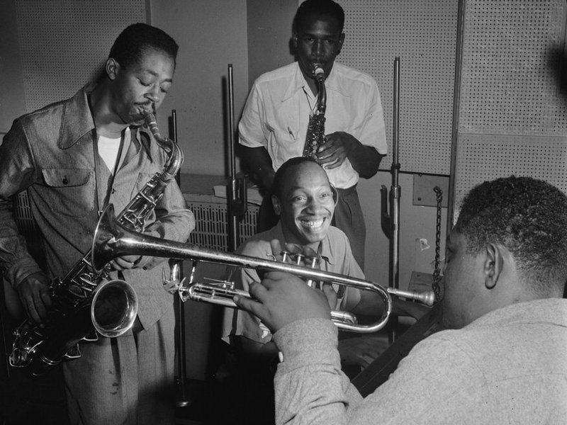 Tadd Dameron (smiling at center) was an important figure in American jazz and bebop. He is shown here with Fats Navarro on trumpet, and Charlie Rouse and Ernie Henry on saxophone.William Gottlieb/Library of Congress.