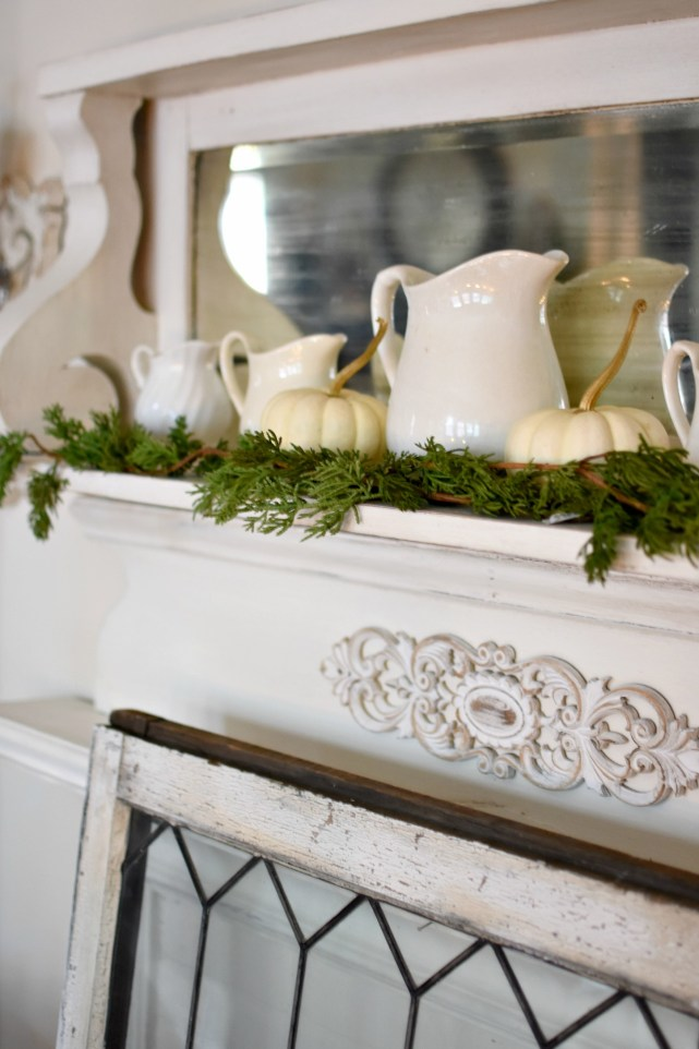 Beautiful shabby chic fireplace decorated for Thanksgiving ironstone pitchers, cedar garland and white pumpkins