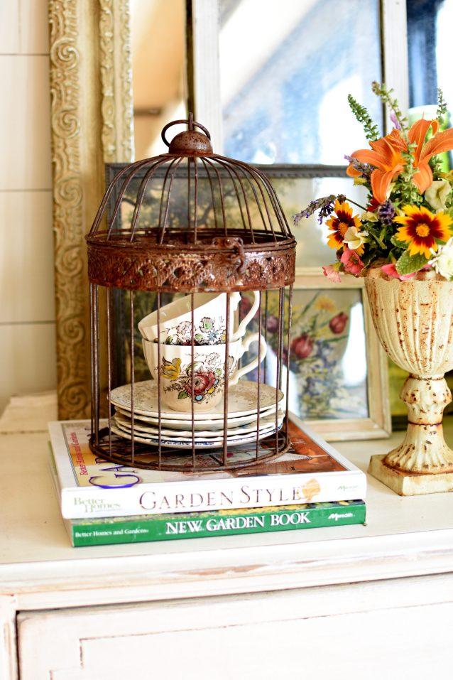 vintage garden vignette teacups in rusty birdcage flower bouquet