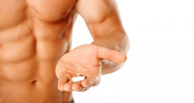 homem com comprimido na mão - O que são os suplementos termogênicos? Quais são os seus riscos?