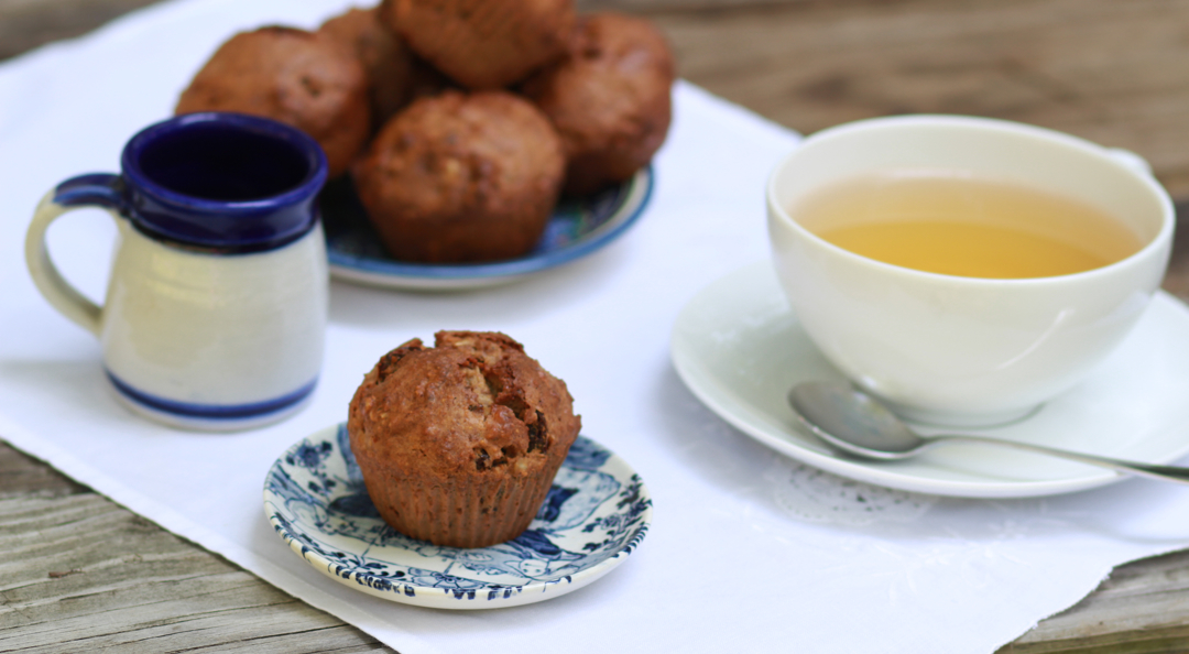 a muffin on a little plate, a cup of tea, a jar of milk and more muffins on the background