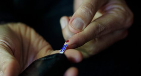 man's hands, testing blood glucose