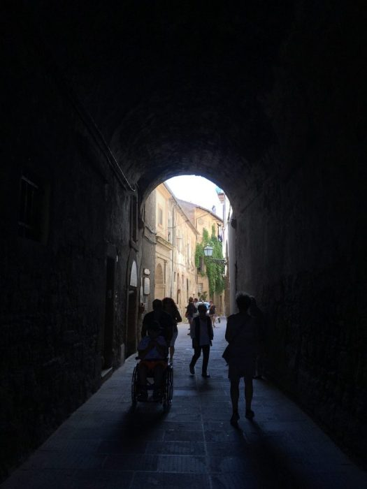 Group of people walking in a narrow street in Pitigliano