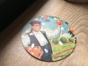 Drink mat with illustration of a Valencian peasant picking oranges