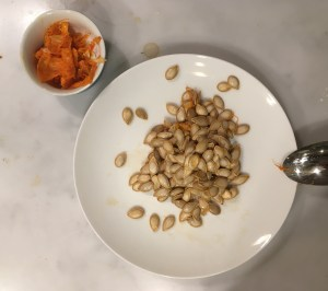Butternut squash seeds in a dish, with pulp on a small pot