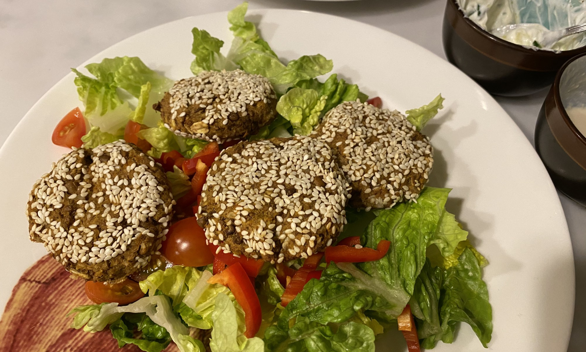 Lentil patties on top of a salad with lettuce, red pepper and tomatoes