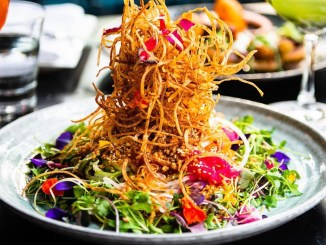 Singaporean-Style Signature Slaw from Lee in Toronto. Plated on a grey ceramic plate and piled high with fried components of tarot root, vermicelli, & shallots. Pickled red onion & ginger. Julienned vegetables like daikon, jicama, green onion, cucumber, carrots & tomato. Edible flowers, toasted sesame seeds, roasted peanuts, daikon sprouts, fennel, purple basil, & coriander herbs.