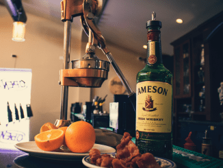 A green bottle of Jameson Irish whiskey, a plate of crispy bacon, a copper juice press and plate of fresh cut oranges cut in half waiting to be squeezed.