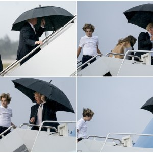 Donald Trump holds an umbrella over himself as he, Melania and Barron board Air Force One