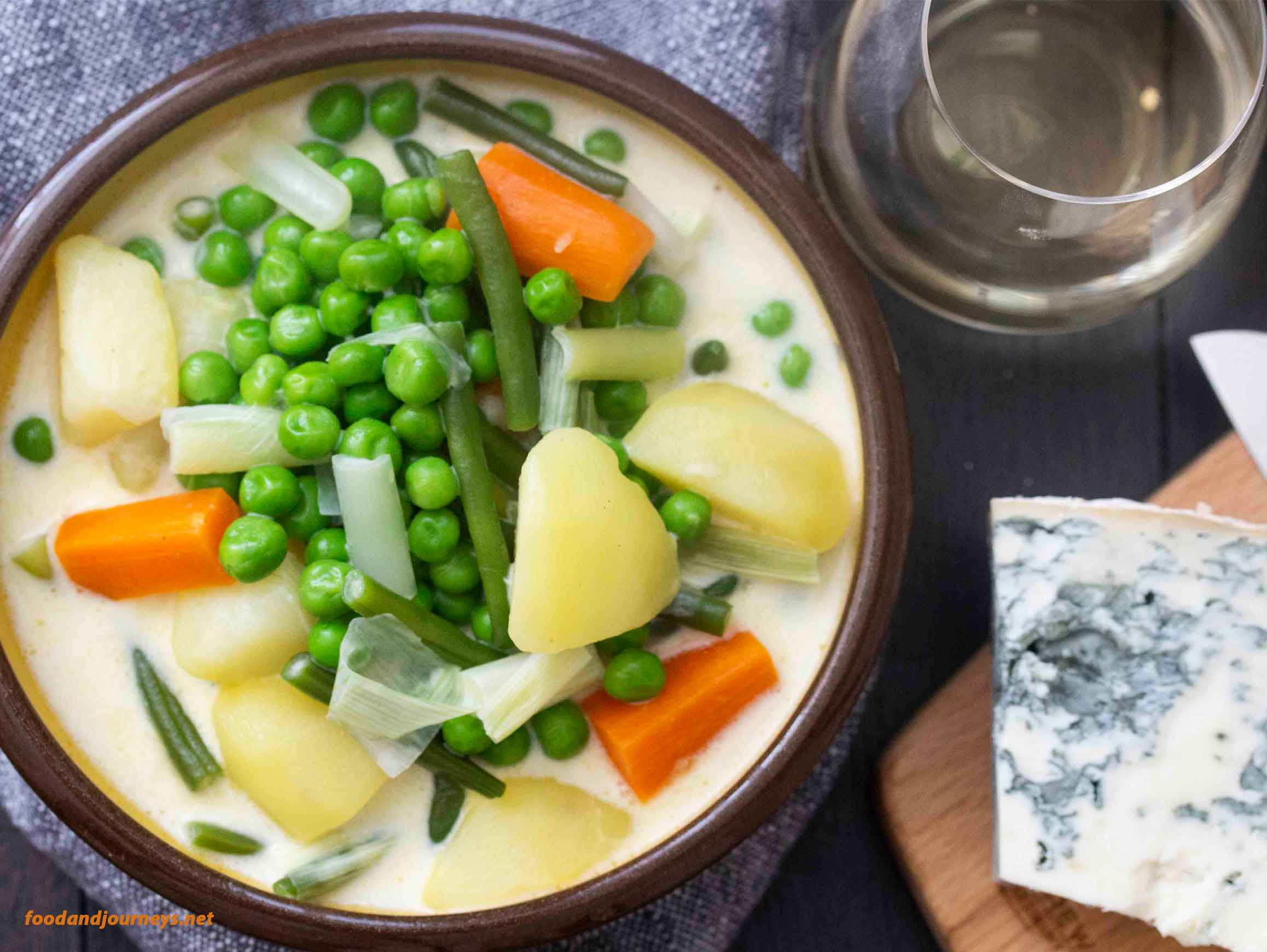 Overhead shot of a serving of Finnish Summer Soup, with a platter of cheese on the side and a glass of white wine.