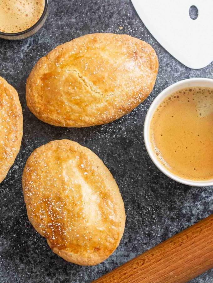 Overhead shot of Italian Cream Filled Pastry (Pasticciotto), with a cup of coffee and a shot of espresso on the side.