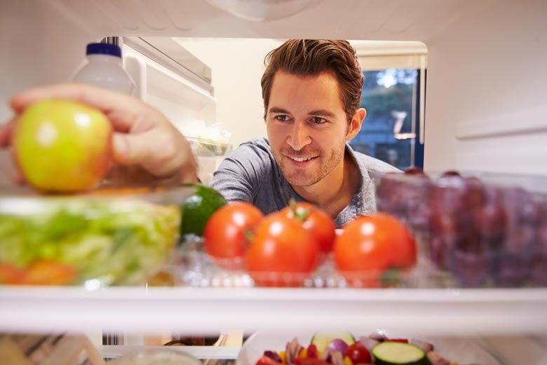 Man reaching into a refrigerator full of healthful food choices