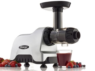 Juicer with glass of juice, strawberries and blueberries