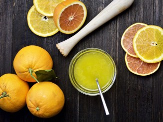 Fresh citrus produce and small glass jar of citrus vinaigrette on dark wood background