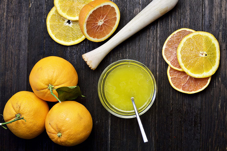 Fresh citrus produce and small glass jar of citrus vinaigrette on dark wood background