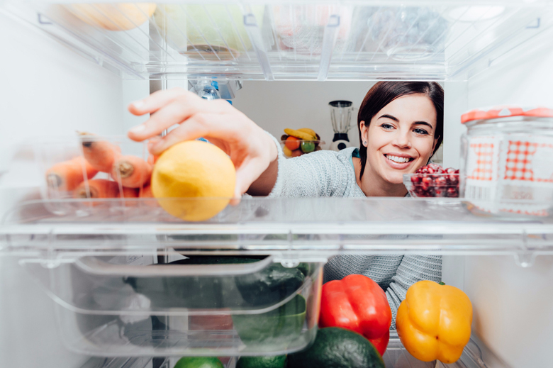 Women reaching into back of fridge to grab lemon