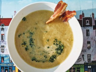 A white bowl of Farm Stand Corn Chowder with Garlic Scape Gremolata & Crispy Bacon on a light sky blue background