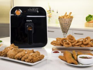 KRUPS Fry Delight air fryer on countertop surrounded by snack foods