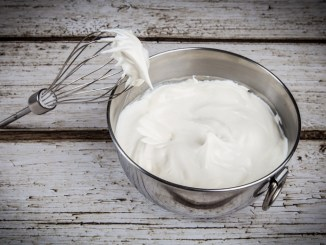 Bowl of whipped cream and whisk