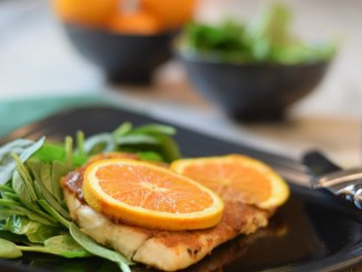 Barramundi fish dish garnished with orange slices and a spinach salad