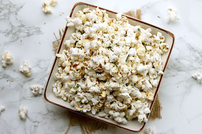 Miso Butter Popcorn in a square bowl on marble background; pieces of popcorn scattered around