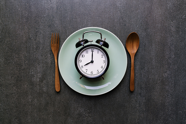 Food clock spoon and fork, Healthy food concept on black background