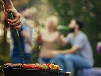 Shot of a hand flipping meat on a barbecue